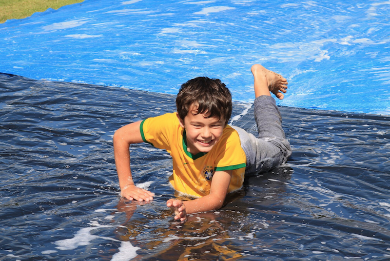 child enjoying a water slide at a summer in the city holiday camp